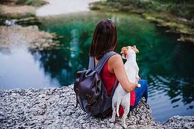 Woman with backpack embracing dog while sitting on rock at lake - p300m2251328 by Eva Blanco
