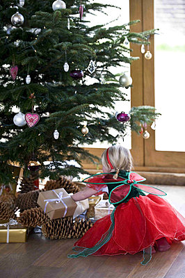 Young girl dressed up looking at the Christmas tree - p349m790659 by Polly Eltes