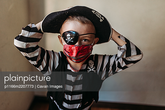 Portrait of school age young boy dressed as pirate with face mask on - p1166m2207773 by Cavan Images