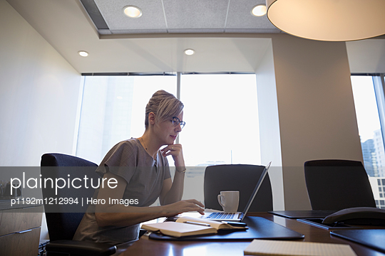 Focused female lawyer working at laptop in conference room