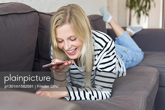 Junge Frau mit Smartphone auf dem Sofa - p1301m1582591 von Delia Baum