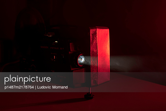 Super8 film in a dark red room - p1487m2178764 by Ludovic Mornand