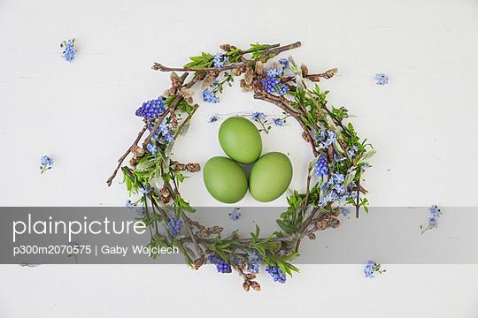 Self-made Easter wreath and green dyed eggs on white ground - p300m2070575 von Gaby Wojciech