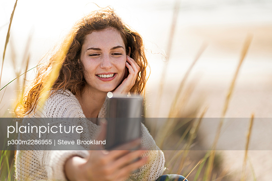 Smiling woman taking selfie through smart phone in dunes at beach during sunny day - p300m2286955 by Steve Brookland