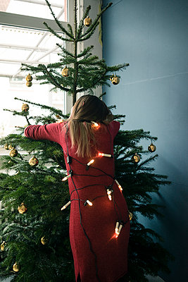 Back view of woman hugging Christmas tree - p300m2003971 by Robijn Page