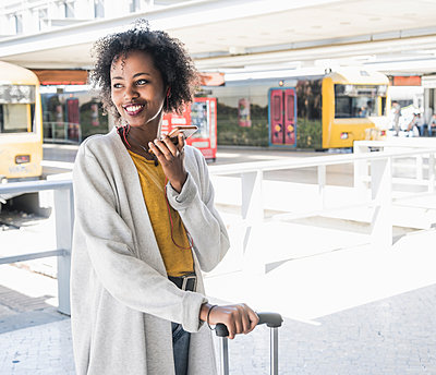 Happy young woman with earphones using smartphone at station platform - p300m2155838 von Uwe Umstätter
