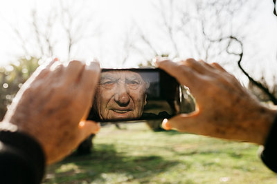 Spain, Barcelona. Retired senior man taking photos with his smartphone in a park and his face reflected on the screen - p300m2166546 von Josep Rovirosa