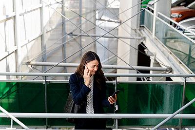 Female professional talking on smart phone while standing near railing - p300m2287382 by Francesco Morandini
