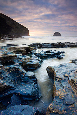 Eroded slate rocks on the beach at Trebarwith Strand, looking towards Gull Rock, Cornwall, England, United Kingdom, Europe - p8713033 by Adam Burton