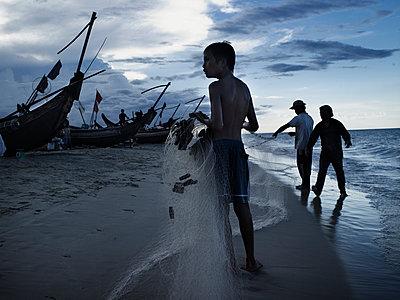 Two men and a young boy tend to a fishing net extending from a fishing boat on shore, Dong Hoi, Quang Binh Province, Vietnam, Southeast Asia - p934m893013 by Boris Zuliani
