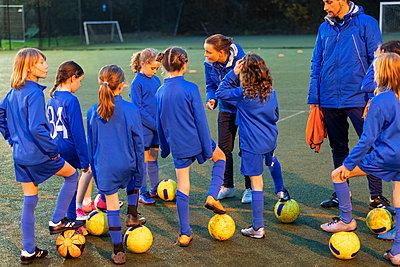 Girls soccer team listening to coaches on field - p1023m2035259 by Paul Bradbury