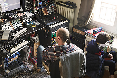 Father and son in home music studio during Covid-19 quarantine - p1499m2179033 by Marion Barat