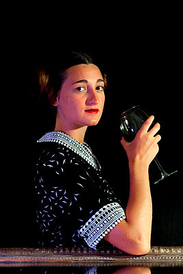 Young woman in retro dress holding a glass of wine - p1521m2108366 by Charlotte Zobel