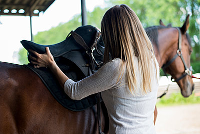 Young woman applying saddle at horse's back - p300m1449707 by ZoneCreative