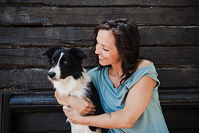 Happy woman hugging Border Collie while sitting in front of cottage - p300m2293411 by Eva Blanco