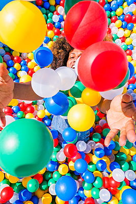 Happy young man playing in vibrant ball pool - p301m2075615 by Sven Hagolani