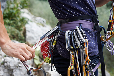 Cropped view of woman climber preparing safety harness with carabinas - p429m1135435f by Violeta Beral