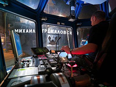 Worker driving tugboat from wheelhouse - p429m747069f by Monty Rakusen