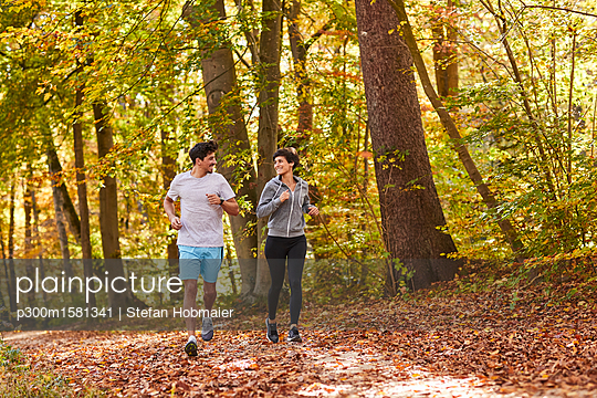 Couple jogging on autumnally forest track - p300m1581341 von Stefan Hobmaier