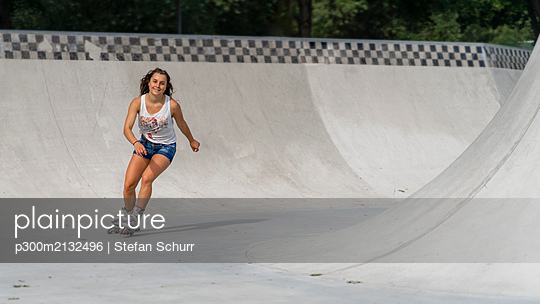 Young woman inline skating in skatepark - p300m2132496 by Stefan Schurr