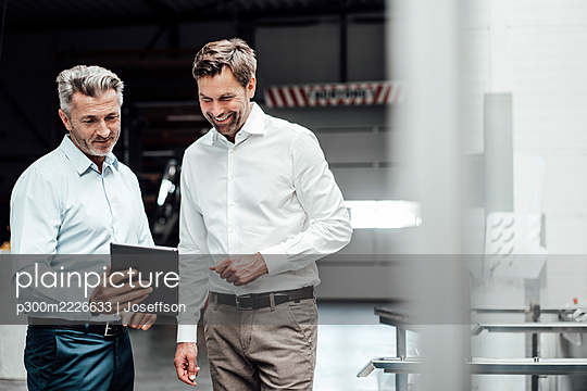 Smiling businessmen discussing over digital tablet while standing in industry - p300m2226633 by Joseffson