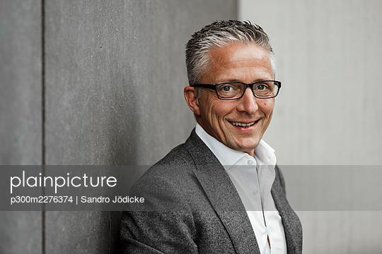 Happy male investor in balzer jacket - p300m2276374 by Sandro Jödicke