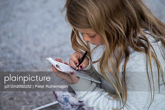 Girl doing notes - p312m2092232 by Peter Rutherhagen