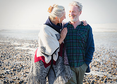 Senior couple hugging and walking on sunny rocky beach - p1023m1106088f by Sam Edwards