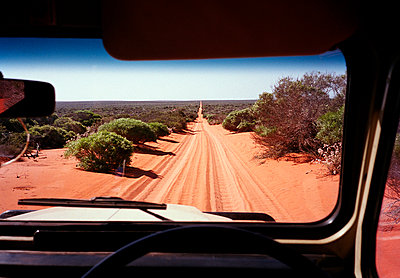 A view of a desert road in Australia through the windshield of an off-road vehicle - p3011578f by fStop