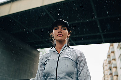 Low angle portrait of female athlete standing against bridge during rainy season - p426m2036791 by Maskot