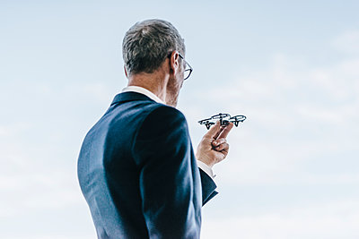 Businessman holding drone in his hand - p586m1208616 by Kniel Synnatzschke