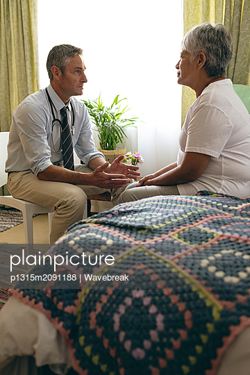 Male doctor interacting with senior female patient - p1315m2091188 by Wavebreak