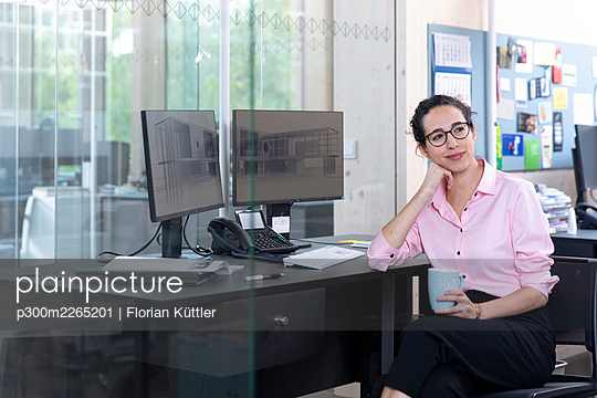 Thoughtful businesswoman with coffee cup sitting at desk in office - p300m2265201 by Florian Küttler