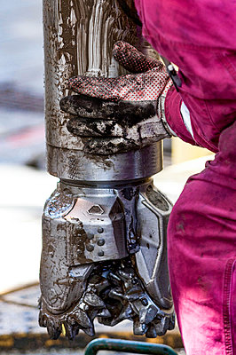 Worker guides drill bit into drill hole on drill floor - p1166m2163037 by Cavan Images