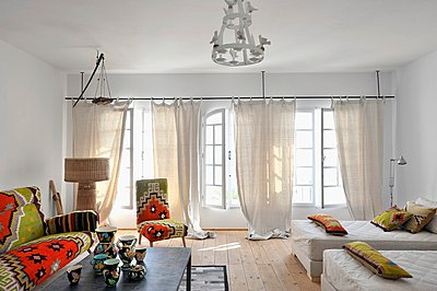"""""""Sofa, chair and scatter cushions with North-African-style covers; patterned chine vases on coffee table"""" - p1183m997594 by Del Olmo, Henri"""