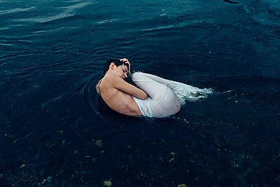 Woman Curled up in Blue Water - p1262m1168931 by Maryanne Gobble