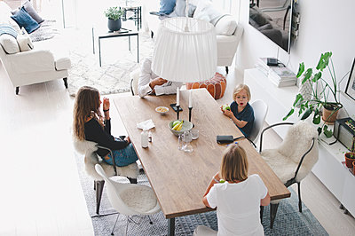 High angle view of family sitting at table in living room - p426m1507219 by Maskot