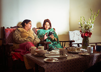 Mother and daughter using cell phone at dinner table - p555m1413098 by Donald Iain Smith