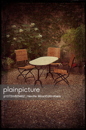 Table and chairs in Parisian garden - p1072m829462 by Neville Mountford-Hoare