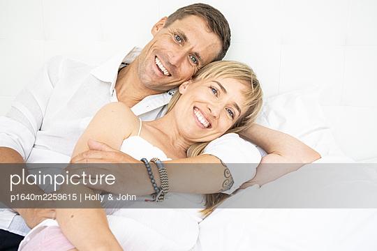 Glückliches Paar liegt auf dem Bett, Porträt - p1640m2259615 von Holly & John