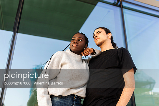 Young couple standing at a glass front looking away - p300m2167066 by Valentina Barreto