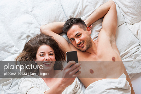 Cheerful woman taking selfie with man while lying in bed at home - p300m2197933 by Daniel Ingold