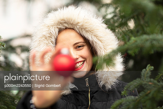 Smiling young woman wearing fur jacket holding Christmas decoration near tree - p300m2243550 by Sigrid Gombert