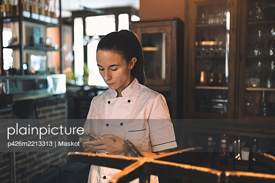Female chef using smart phone in restaurant - p426m2213313 by Maskot
