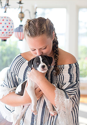 Teen girl with braids holding and kissing a new puppy indoors in Virgi - p1166m2078520 by Cavan Images