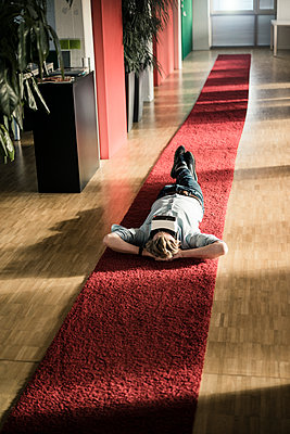 Businessman lying on carpet on the floor in office wearing VR glasses - p300m1535243 by Joseffson