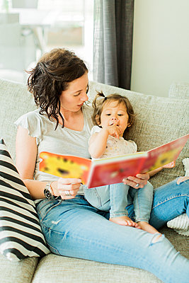 Mother reading childrens book with daughter - p312m2049958 by Alicia Swedenborg