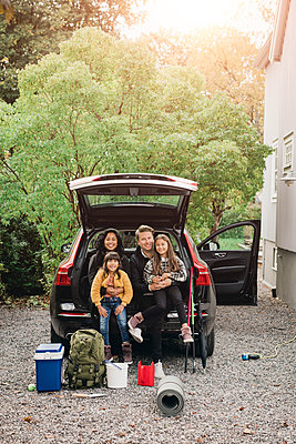 Smiling parents sitting with daughters in trunk of electric car - p426m2194954 by Maskot