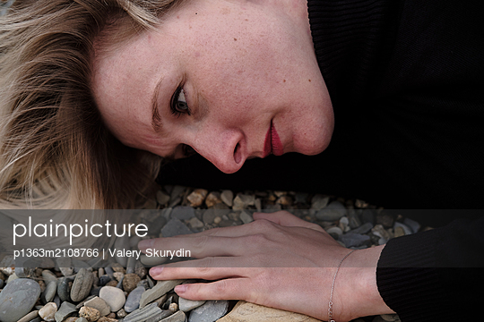 Woman lying on stones - p1363m2108766 by Valery Skurydin
