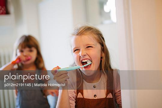 Girl brushing teeth - p312m2191145 by Matilda Holmqvist